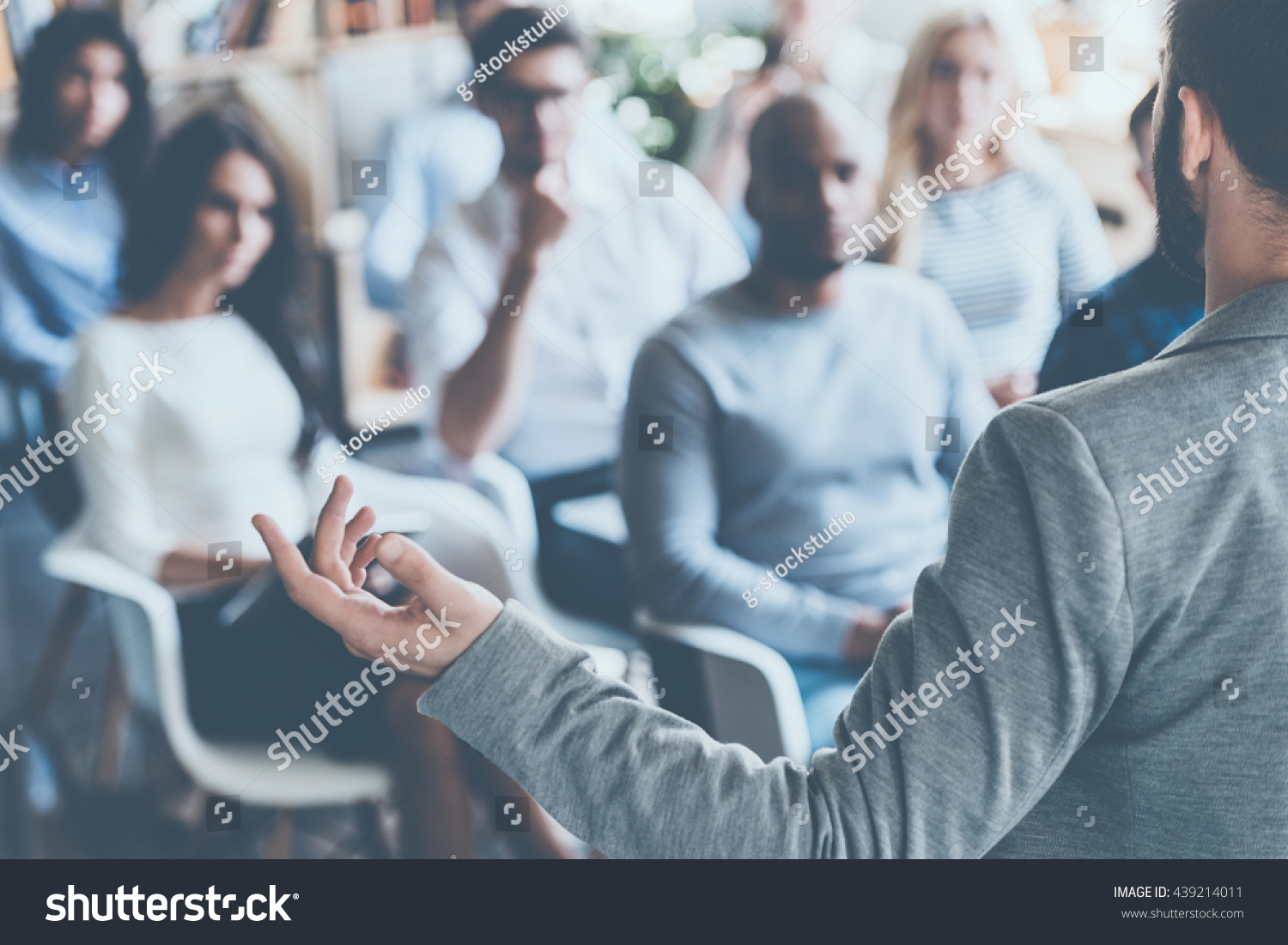 Business coach. Rear view of man gesturing with hand while standing against defocused group of people sitting at the chairs in front of him  #439214011