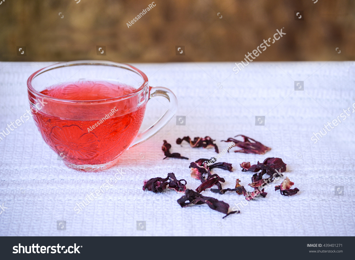 Cup hibiscus tea transparent cup on stock photo 439401271 shutterstock cup of hibiscus tea in transparent cup on white tablecloth beside dried hibiscus flowers izmirmasajfo Images