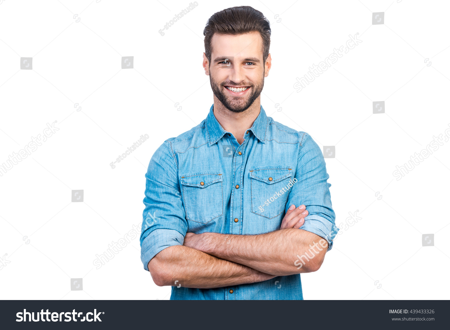 Casually handsome. Confident young handsome man in jeans shirt keeping arms crossed and smiling while standing against white background  #439433326