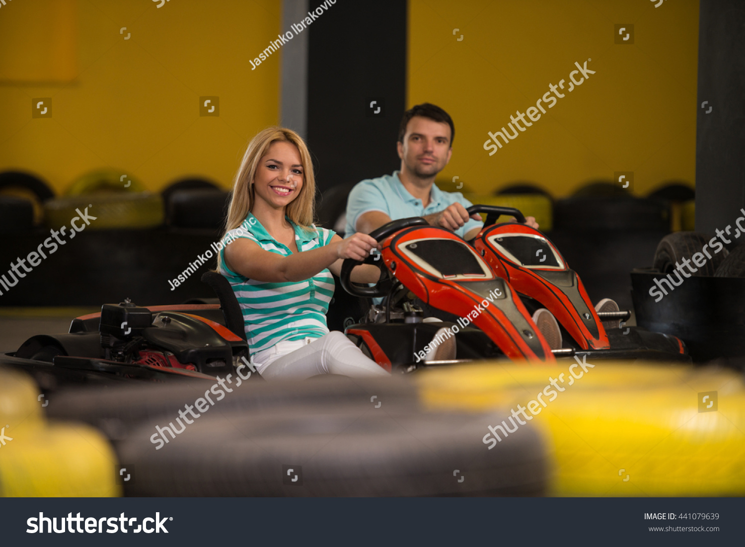 Group Of People Is Driving Go-Kart Car With Speed In A Playground Racing Track Go Kart Is A Popular Leisure Motor Sports