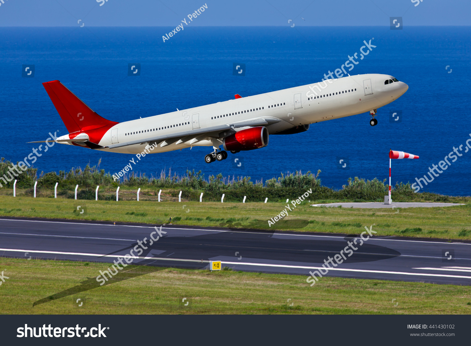 White passenger wide-body airplane with red engines and red tail A few seconds after take-off from the airport runway Aircraft are climbing against the deep-blue ocean