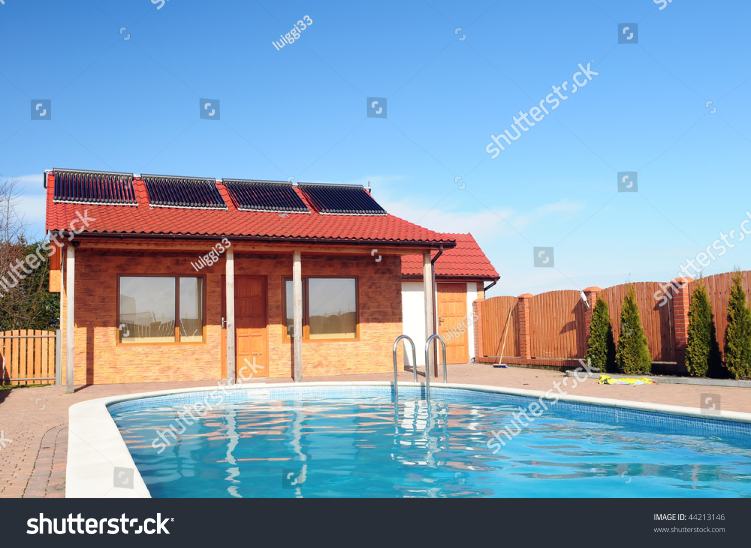 Swimming Pool In Front Of Small Bungalow With Solar Panels On Roof