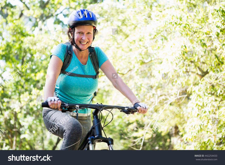 mature woman riding bike on wood stock photo 442254433 - shutterstock
