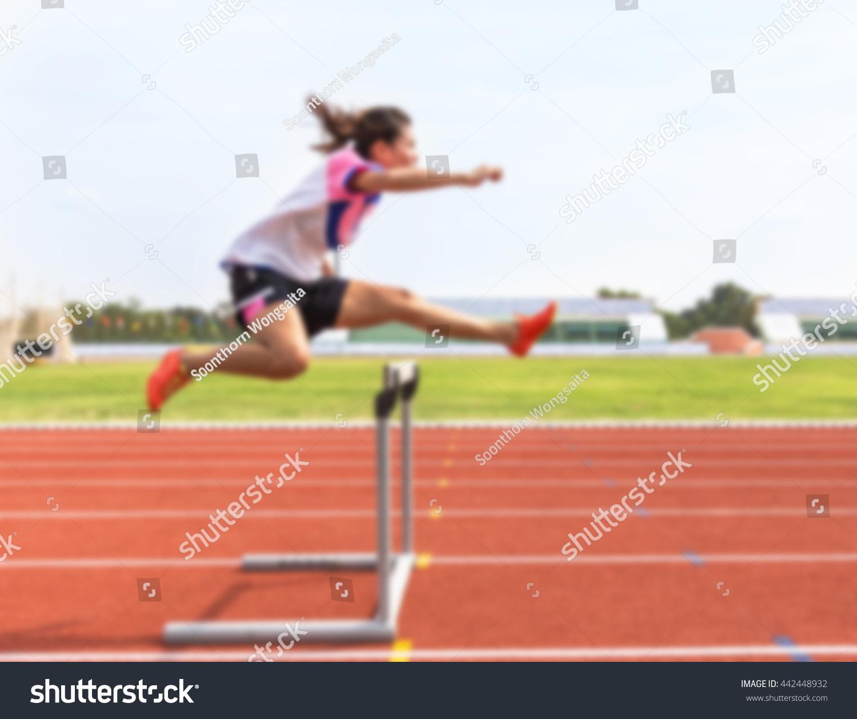 Blurred Female Jump Over Hurdle During Training In Stadium