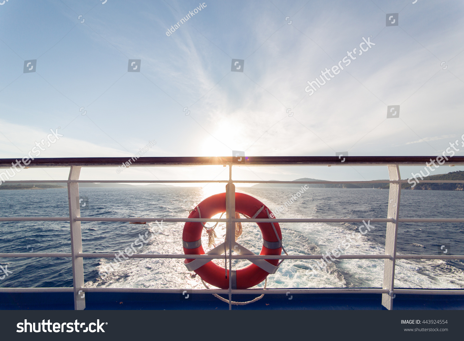 Ring life boy on big boat.Obligatory ship equipment.Personal flotation device.Prevent drowning.Orange lifesaver on the deck of a cruise ship.Traveling to an island #443924554