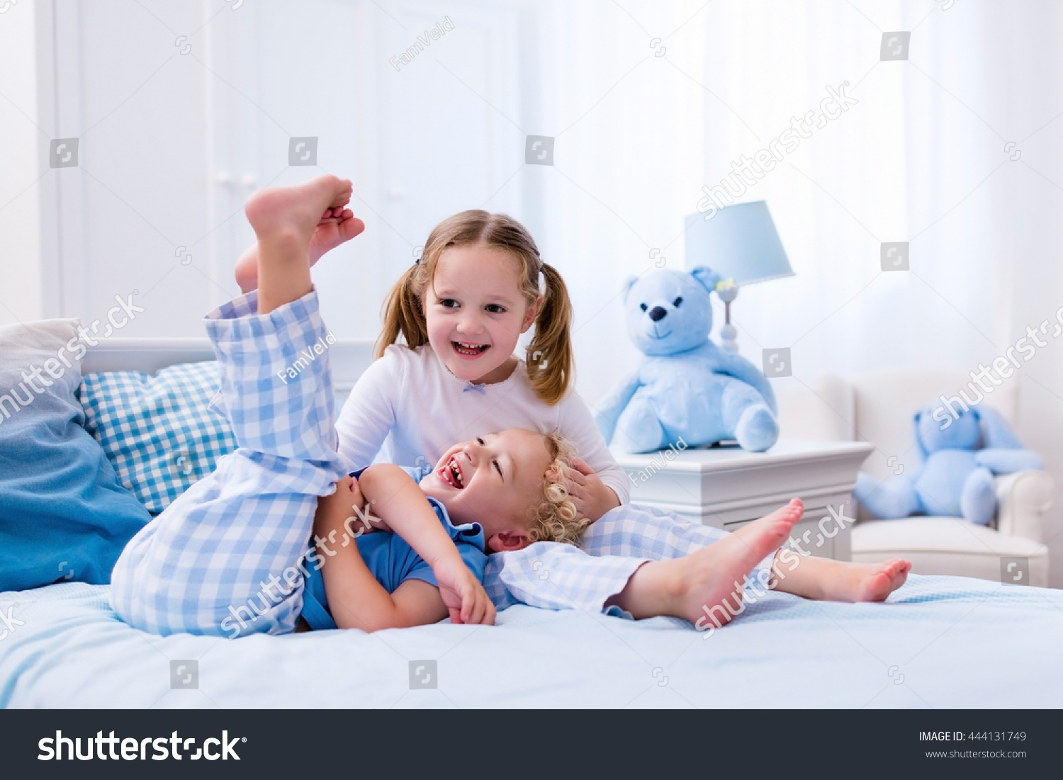 Happy kids playing white bedroom little stock photo for Boys and girls in bed
