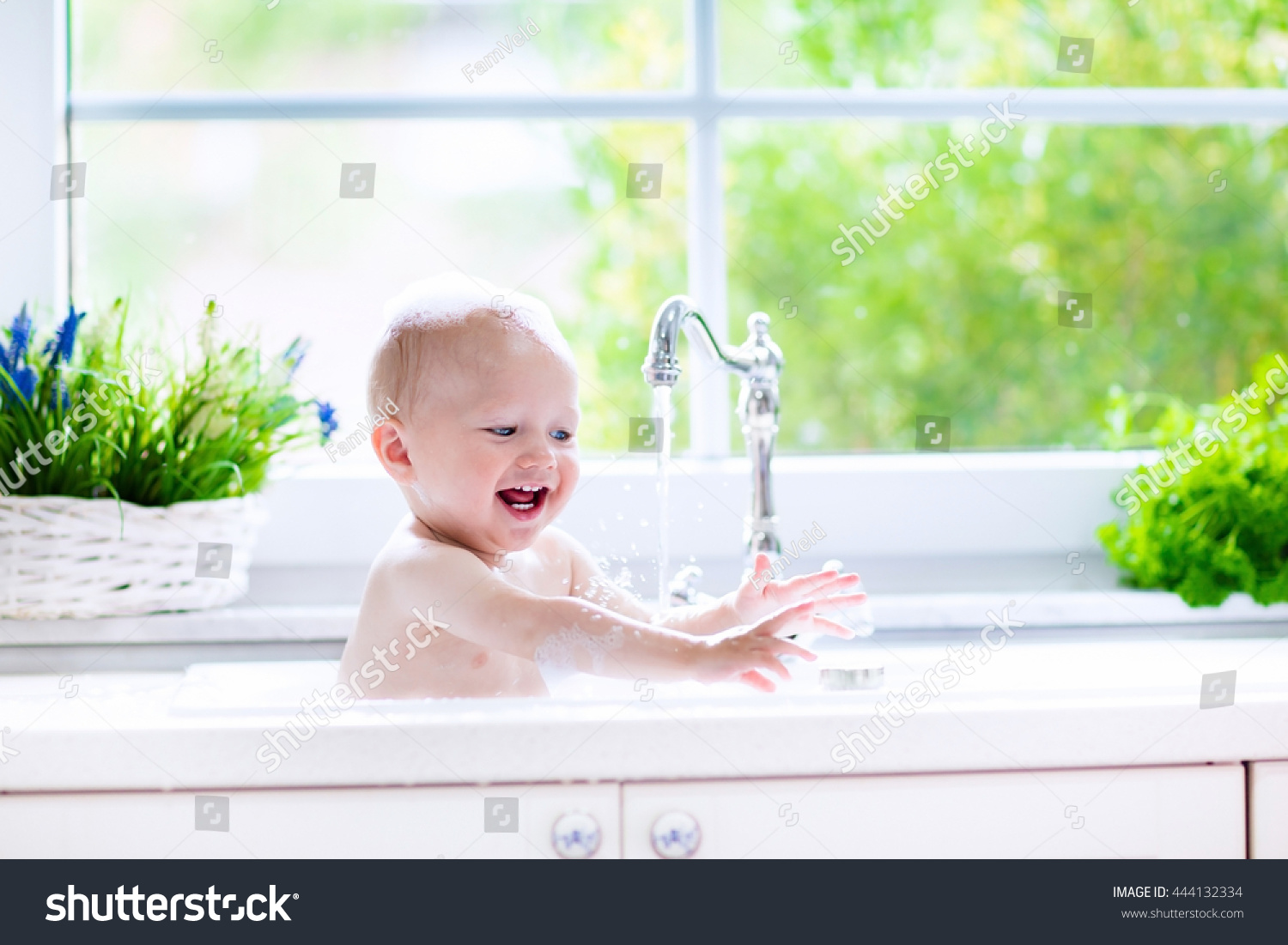 Baby Taking Bath In Kitchen Sink. Child Playing With Foam And Soap Bubbles  In Sunny