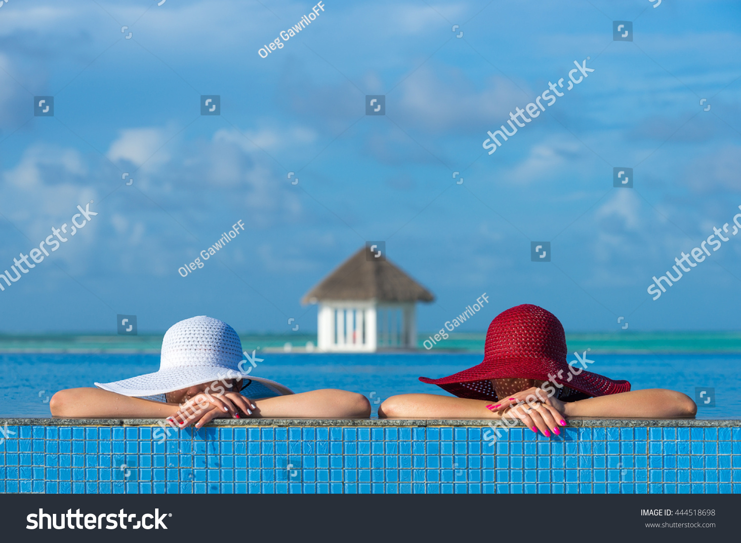 Two women in a hat sitting on the edge of the swimming pool