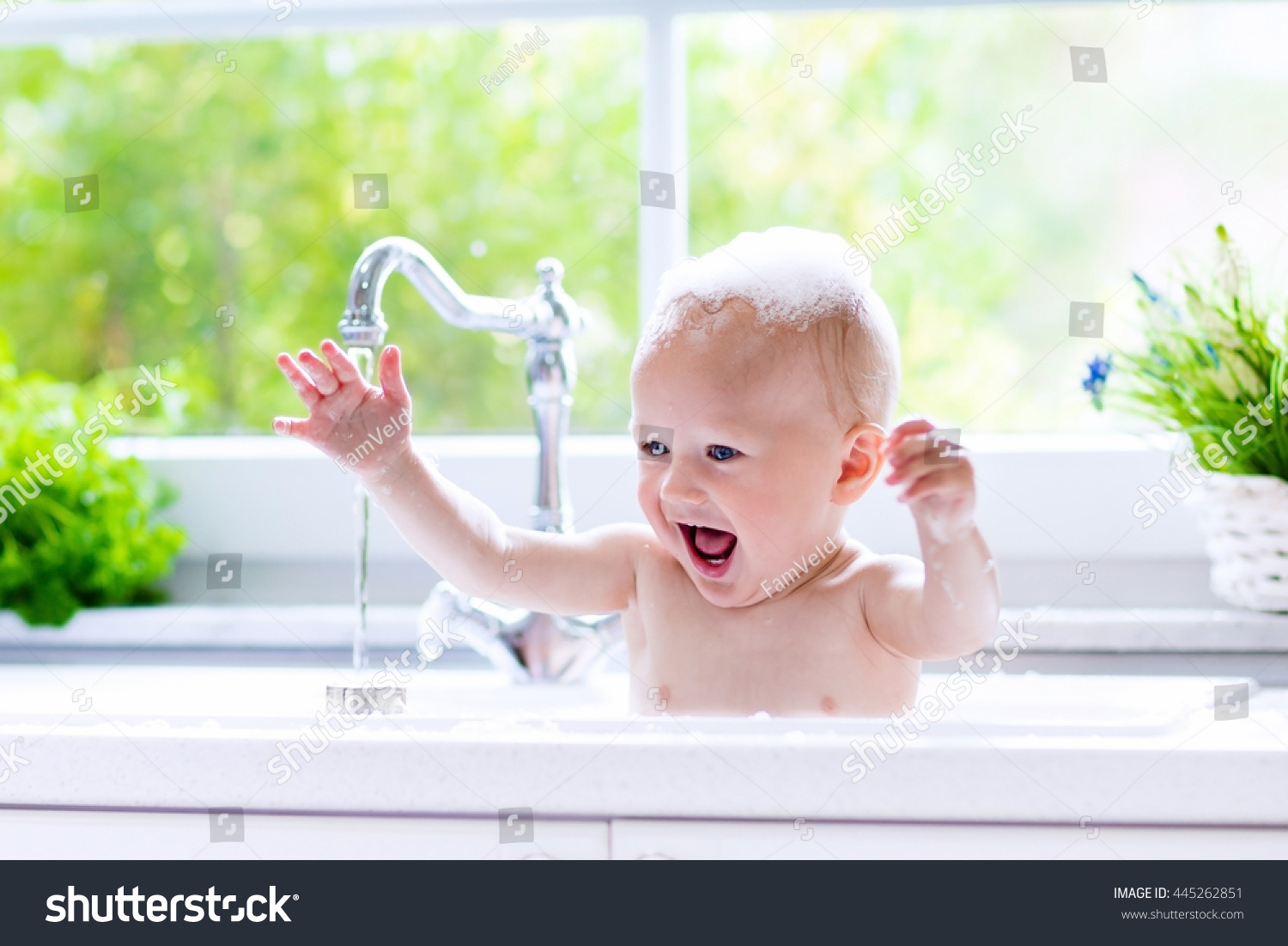 Baby taking bath in kitchen sink  Child playing with foam and soap bubbles in sunny. Baby Taking Bath Kitchen Sink Child Stock Photo 445262851