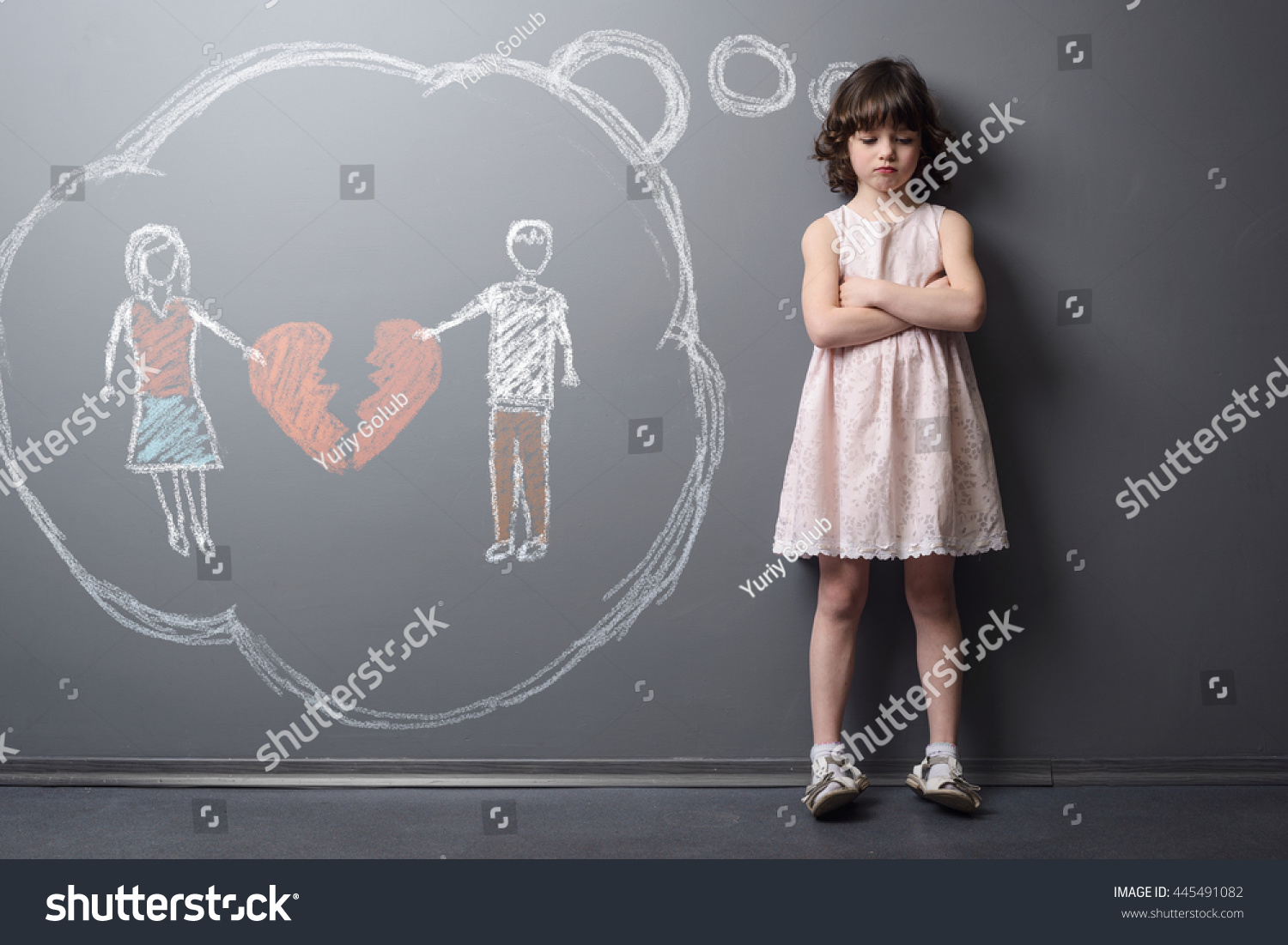 Child with the broken heart. Little girl crossed her hands and looks very unhappy. Depicted divorce of the parents on the grey wall with chalk. Kid suffers after the divorcement. #445491082