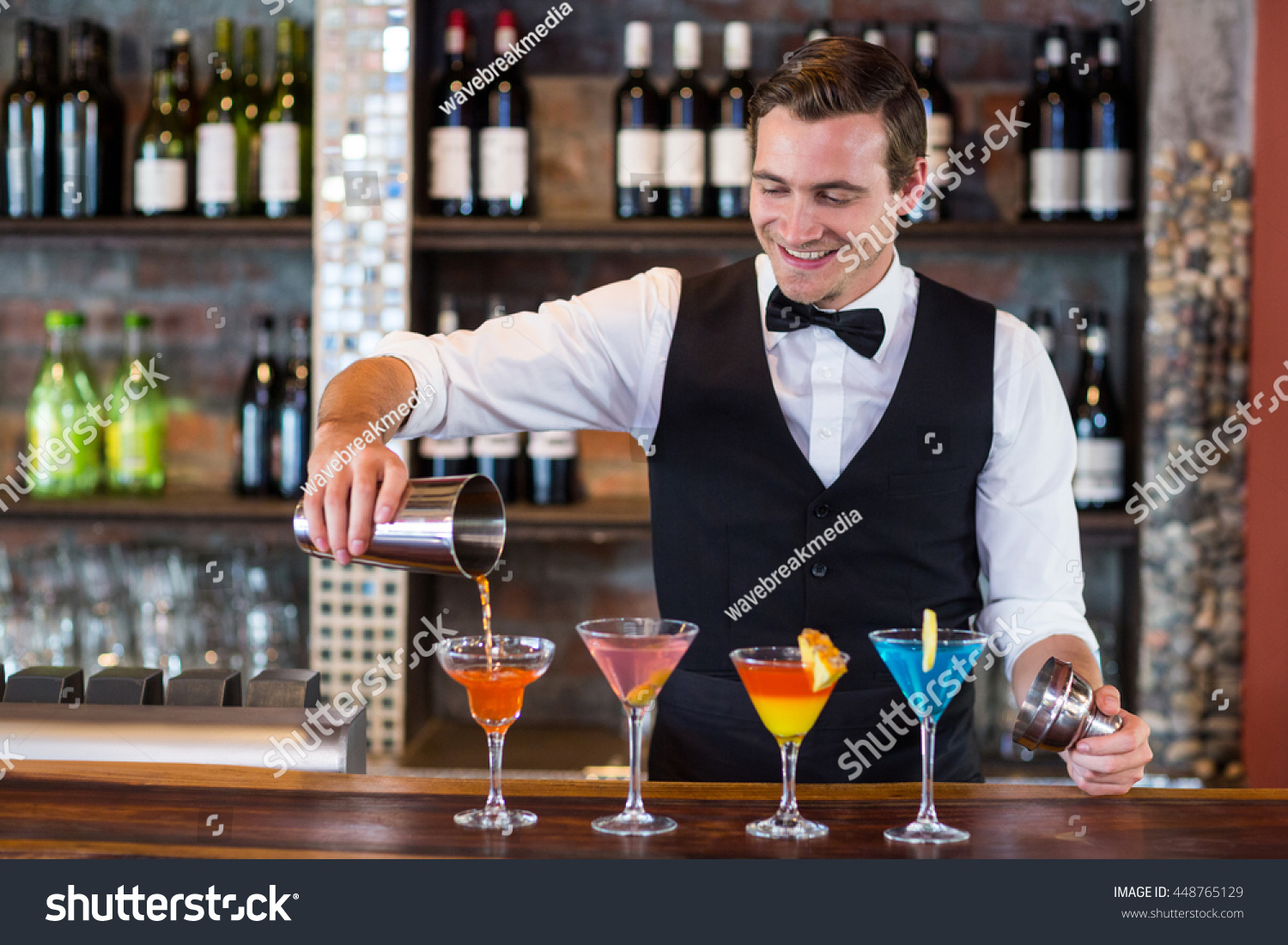 Bartender pouring a orange martini drink in the glass at bar #448765129