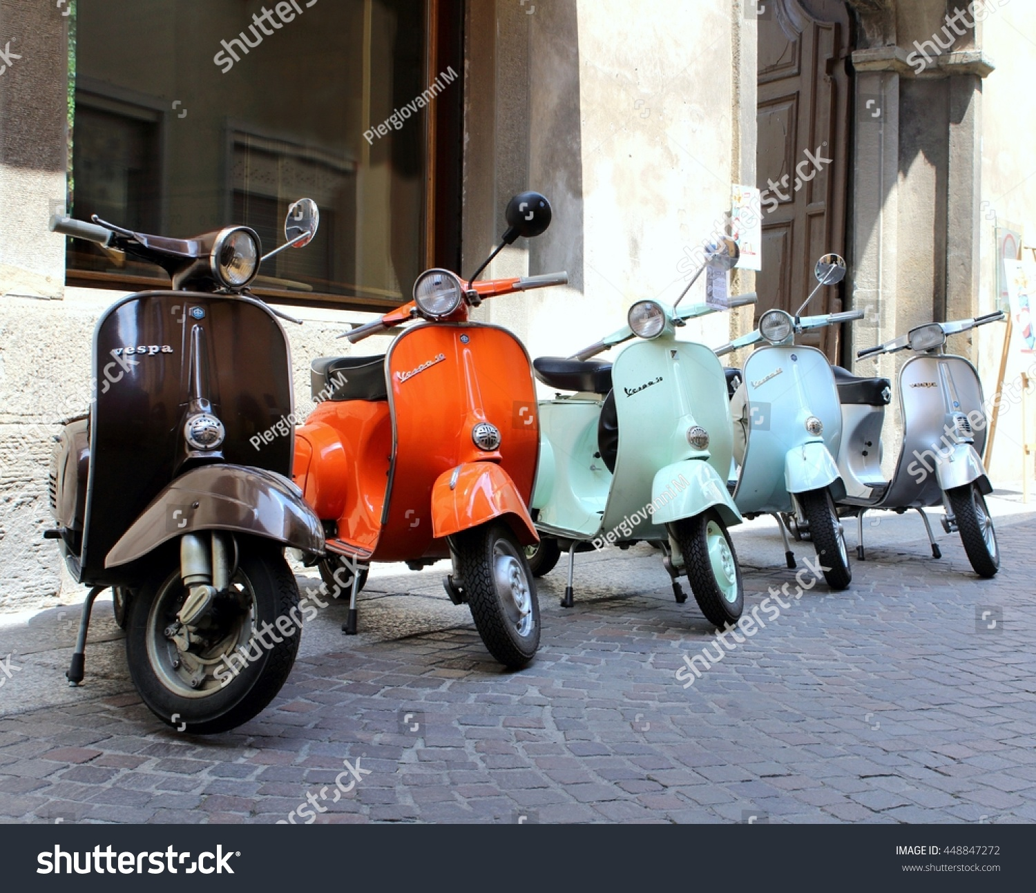 classic italian scooters parked ancient street stock photo