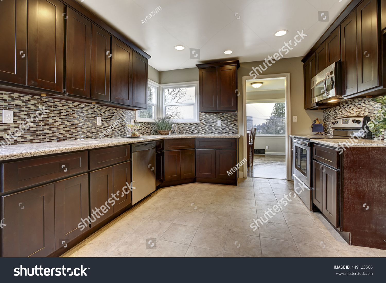 Modern kitchen interior dark brown storage stock photo royalty free modern kitchen interior with dark brown storage cabinets with granite counter tops and new tile floor dailygadgetfo Image collections
