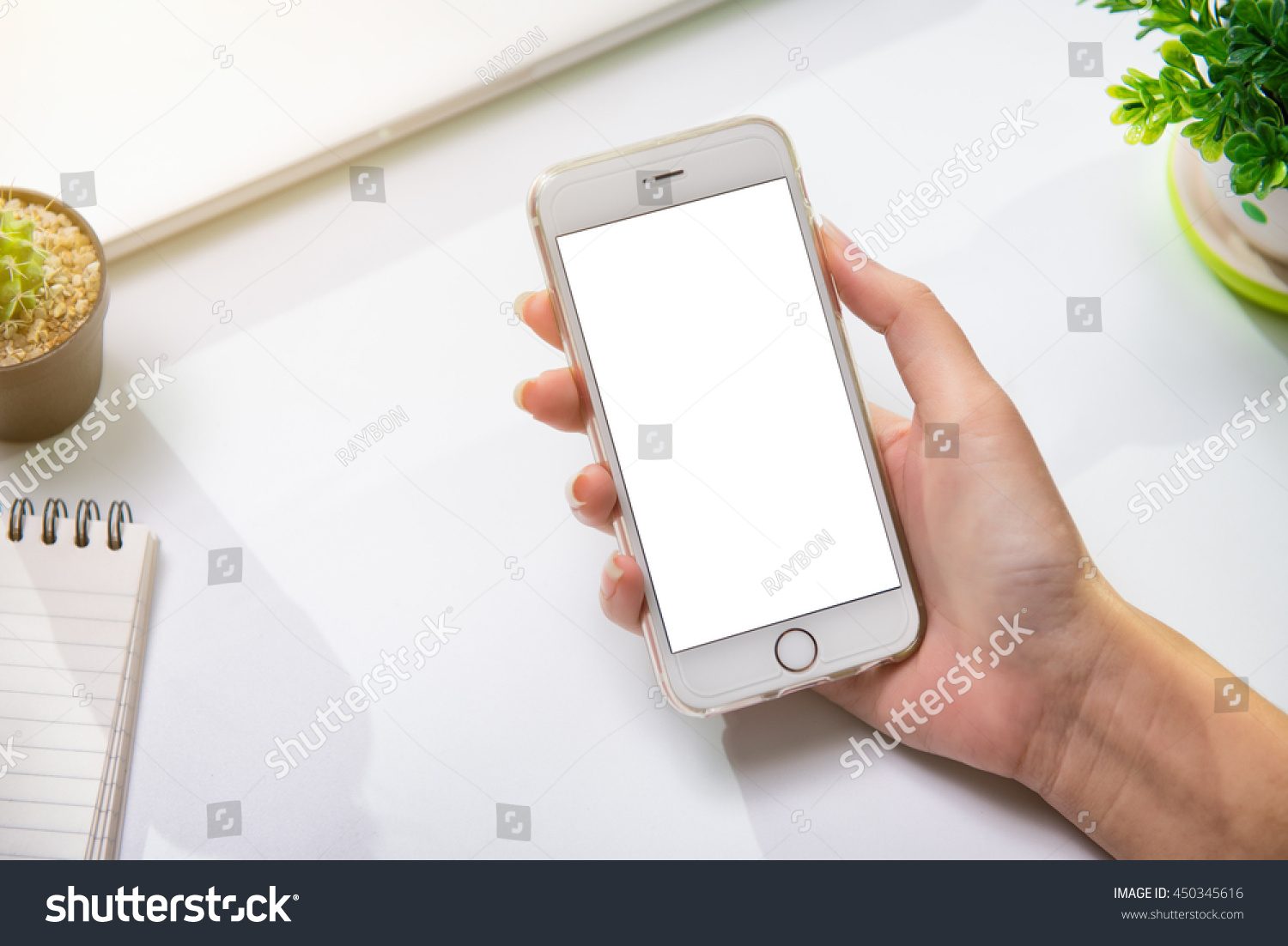 Desk in the office Hand is holding showing smartphone with blank mock up screen over office desk table. This can be used to montage the mobile application. #450345616