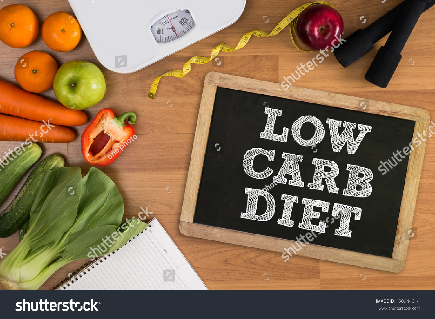 LOW CARB DIET Fitness and weight loss concept, dumbbells, white scale, fruit and tape measure on a wooden table, top view, free copy space #450944614
