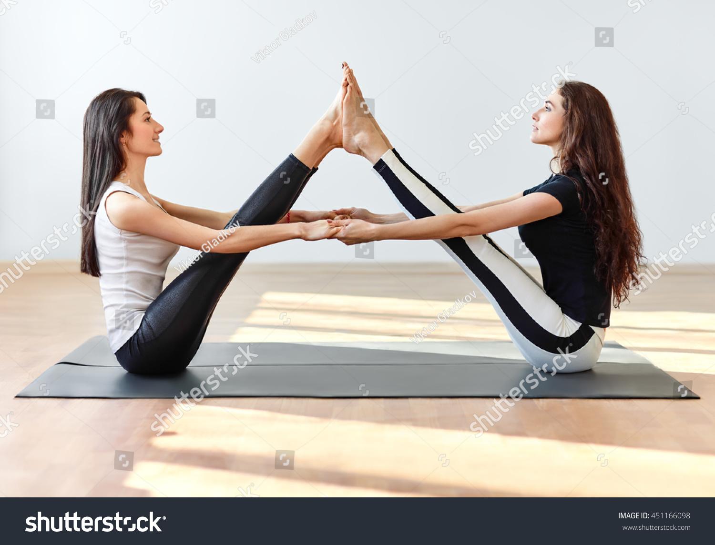 Two Young Women Doing Yoga Asana Buddy Boat Pose ...  Two Young Women...