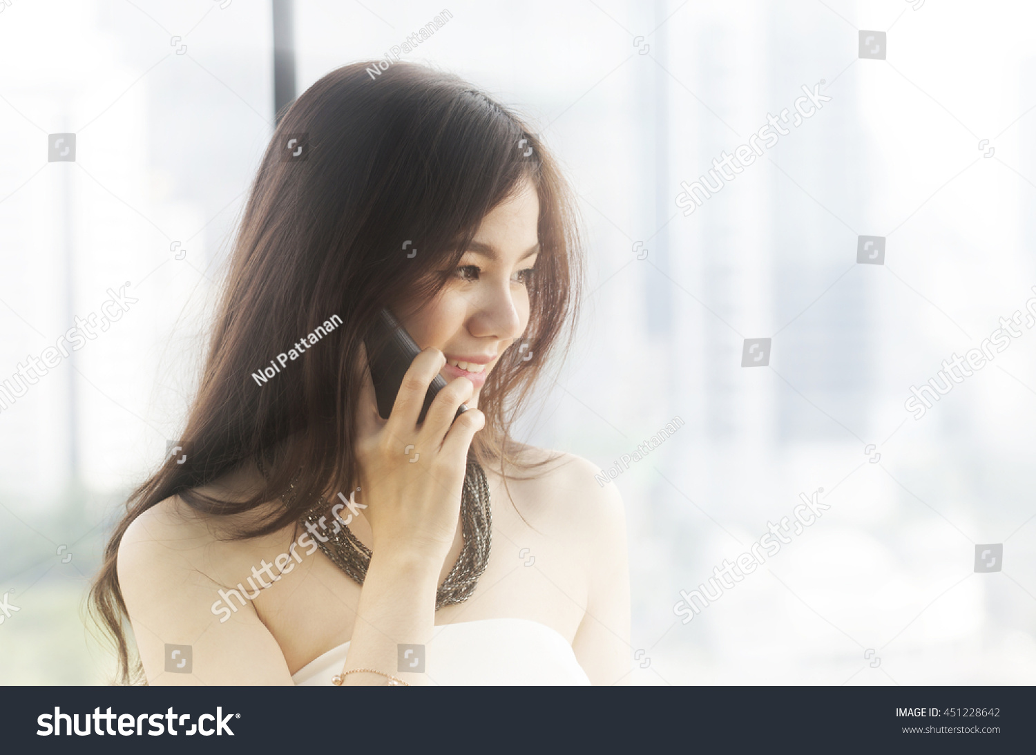 Asian woman talk on a cell phone ,bright background #451228642