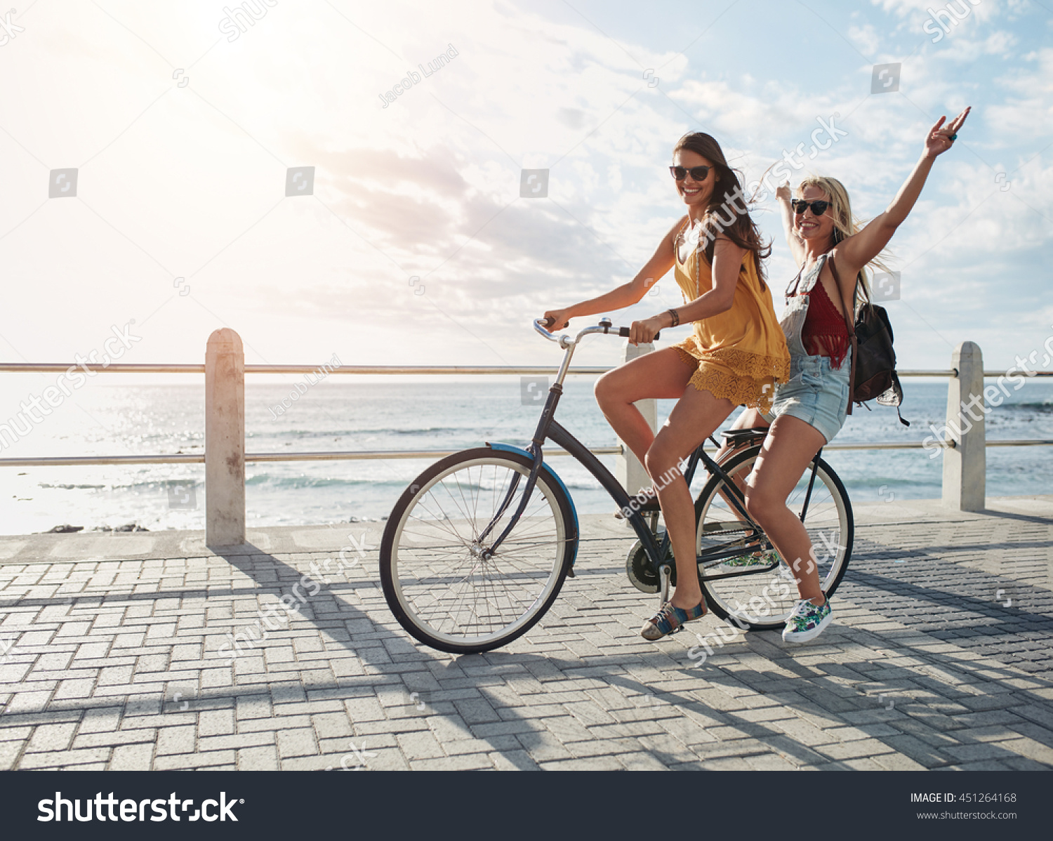 Joyful young women riding a bicycle together. Best friends having fun on a bike at the seaside promenade.