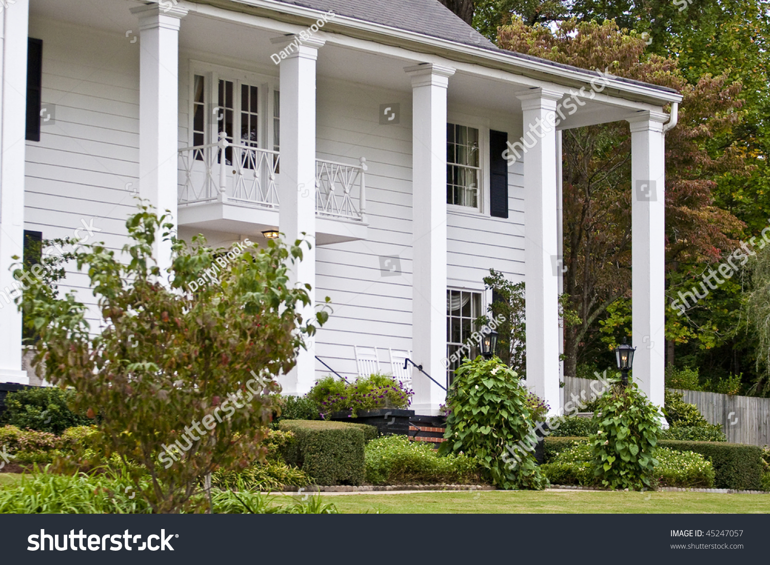an old white siding farm house with columns on front porch