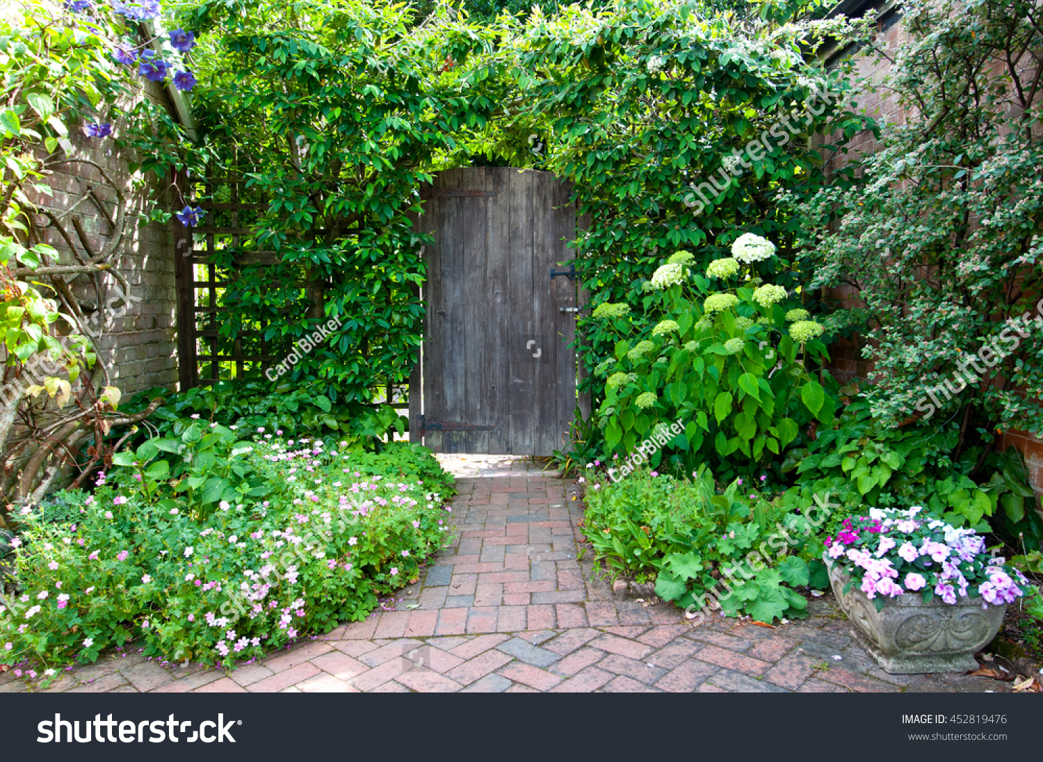 Garden doorway surrounded by flowers herbs and climbing plants with brick paving path. & Garden Doorway Surrounded By Flowers Herbs Stock Photo 452819476 ...