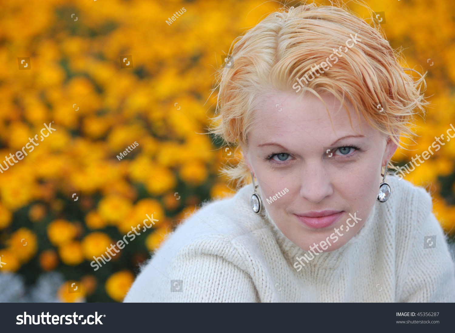 Androgynous look pretty blonde female portrait closeup with a lot of yellow flowers on background. Copyspace.