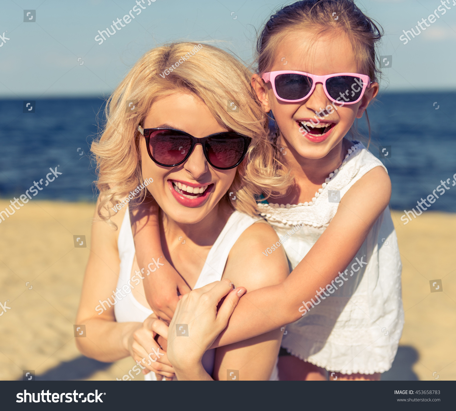 aa66473238fe Portrait of beautiful young mom and her cute little daughter in sun glasses  hugging