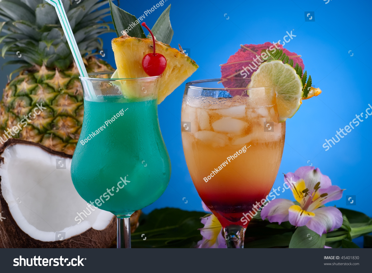 Closeup of Mai Tai and Blue Hawaiian cocktails surrounded by tropical ...