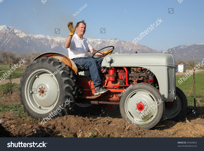 Guy On Tractor : Senior aged man riding on farm stock photo