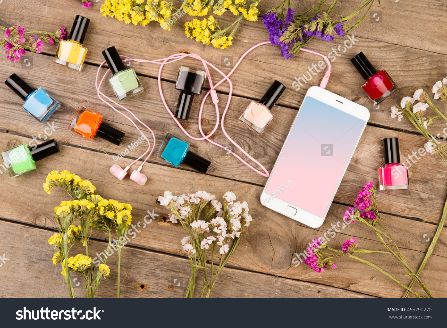 Bottles colorful nail polish smart phone stock photo royalty free bottles of colorful nail polish smart phone headphones and flowers on brown wooden table izmirmasajfo