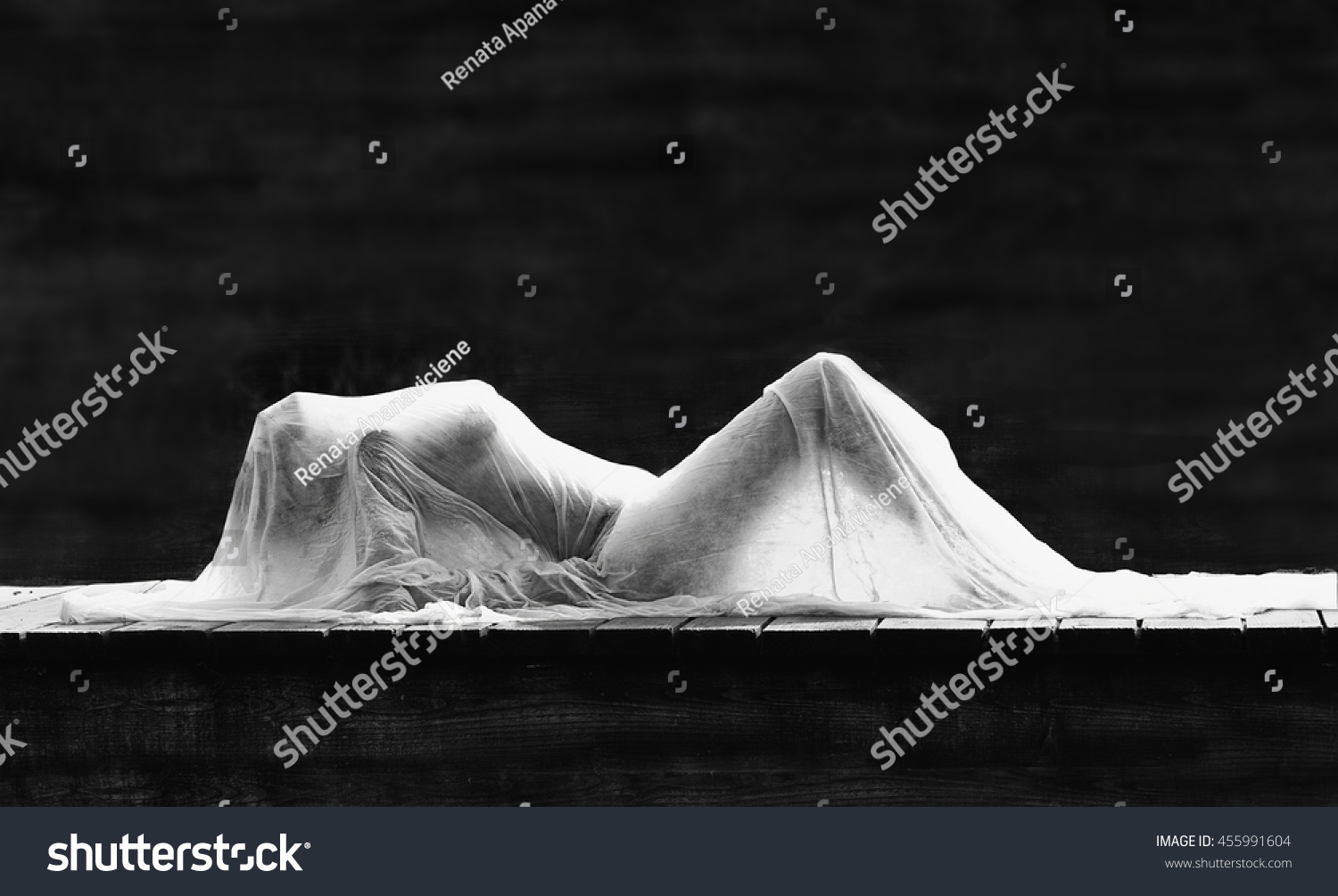 Artistic sensual black and white photo of gorgeous sexy beautiful girl figure hiding in white material silhouette of woman body