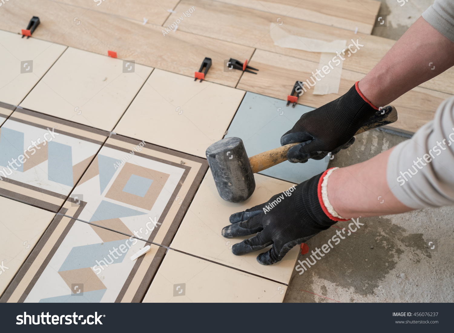 Laying colored ceramic tiles on concrete stock photo 456076237 laying colored ceramic tiles on the concrete floor in the living room of a city apartment dailygadgetfo Choice Image