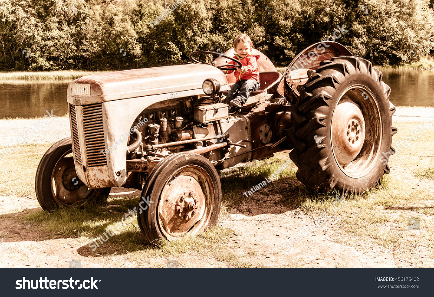 Boy On Tractor : Baby boy on tractor gritty effect stockfoto