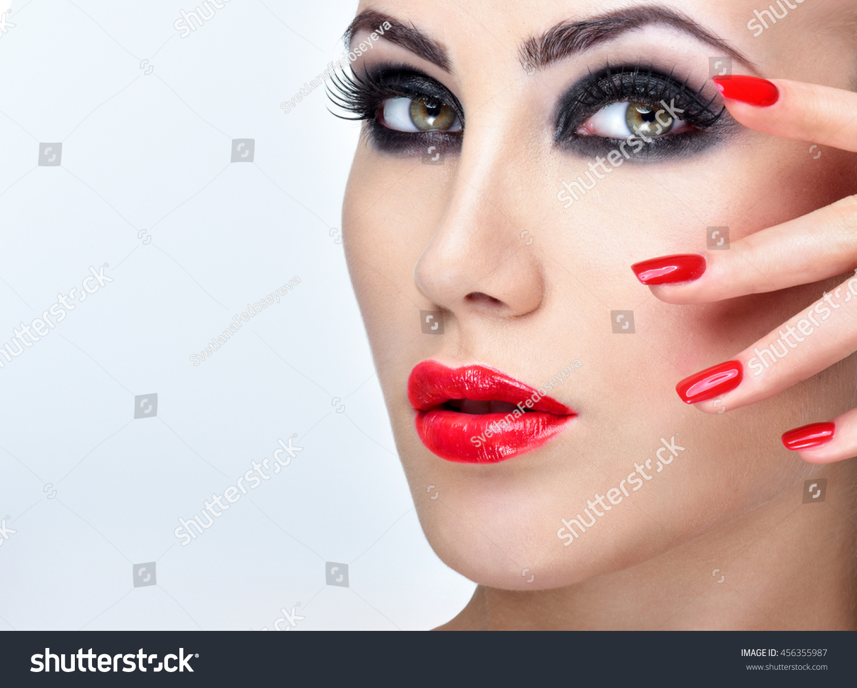 Professional Makeup. Beautiful Fashion Model Girl Face. Perfect manicure. Red Lipstick.