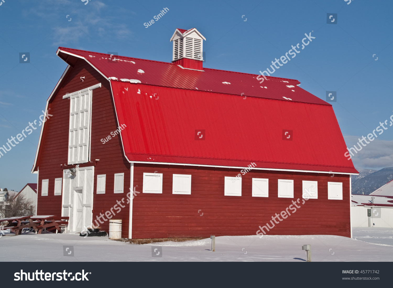 Big Red Barn With White Doors And Trim, A Red Metal Roof, And A