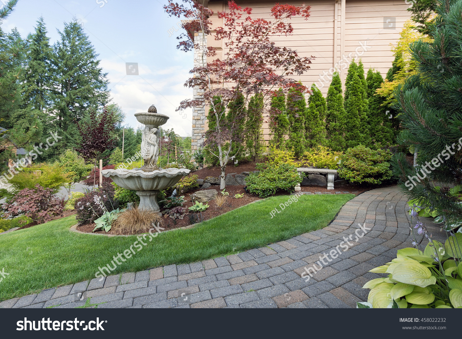 House Manicured Frontyard Garden With Water Fountain Stone Bench Green Lawn  Plants Trees Shrubs And Brick