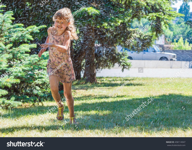child playing garden sprinkler preschooler kid stock photo