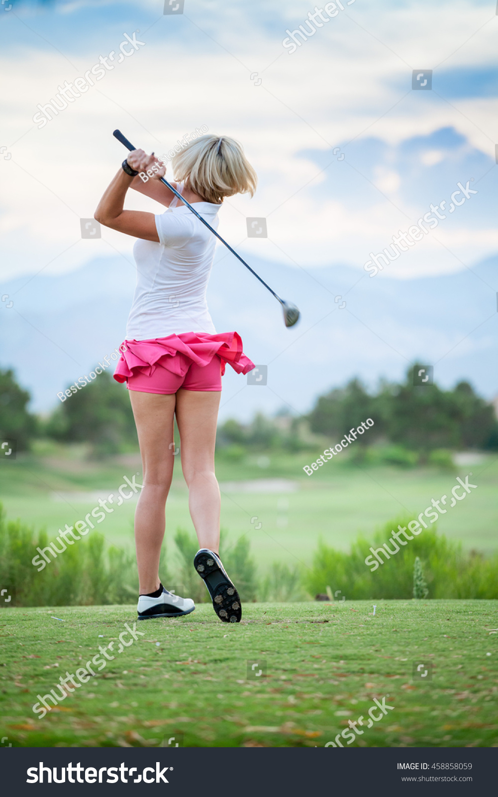 blonde female golfer swinging club on stock photo edit now