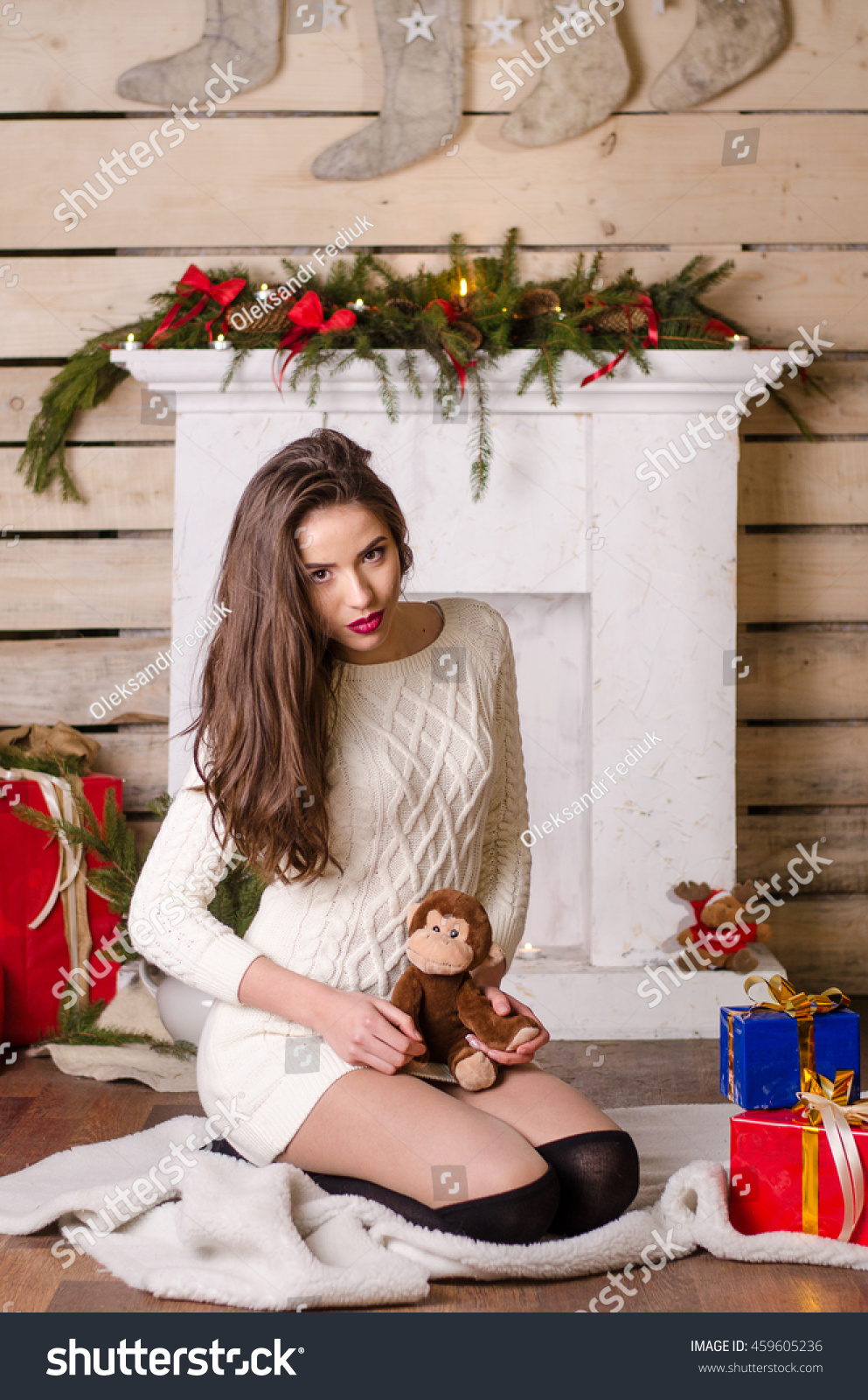 20f75e3c59 Beautiful sexy woman with Xmas tree in background sitting on elegant chair  in cozy scenery.