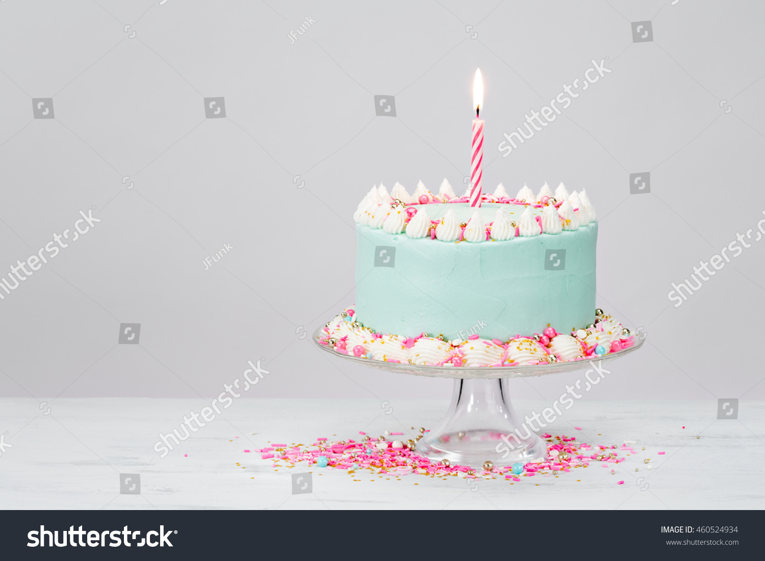 Pastel Blue Birthday Cake With Pink Sprinkles Over White Background