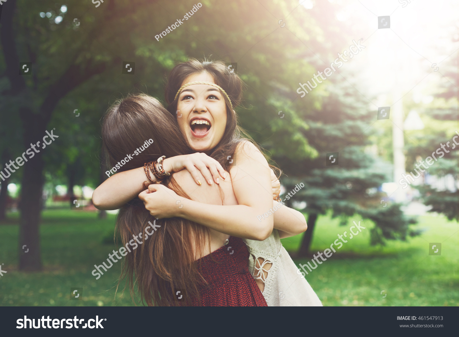 Two happy young girls hug each other Females embracing laughing and excited Woman friendship walk in the park outdoors Asian boho girl with friend