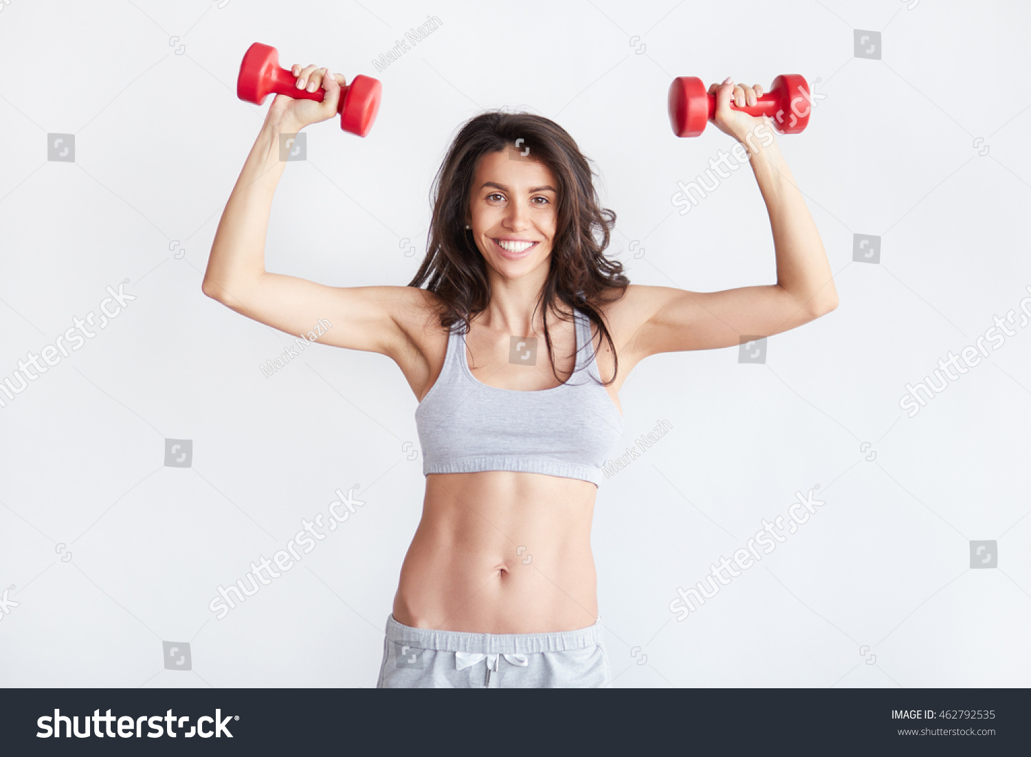 Smiling athletic woman pumping up muscles with red dumbbells isolated on white background. Strong fit brunette female fitness trainer #462792535