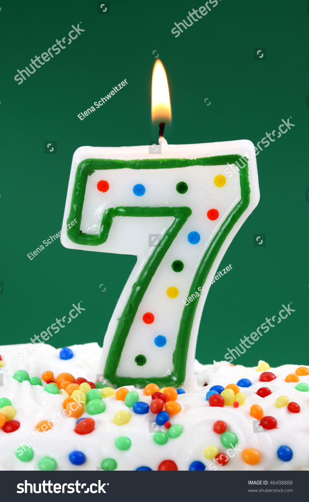Number Seven Birthday Candle On Green Background Stock