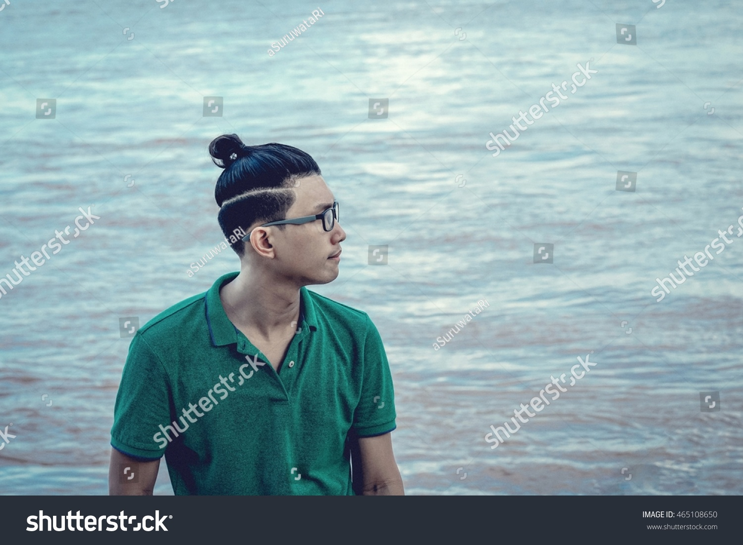 c2eda2c94df Asian hipster glasses man with man bun hair style on river water surface -  lifestyle in
