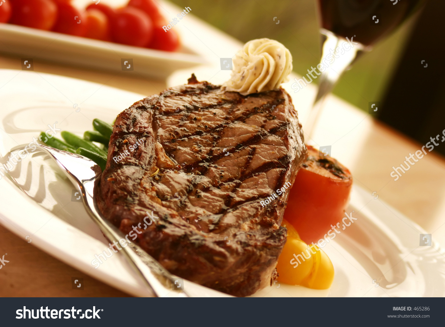steak topped with truffle butter and grilled tomato. Served with red ...
