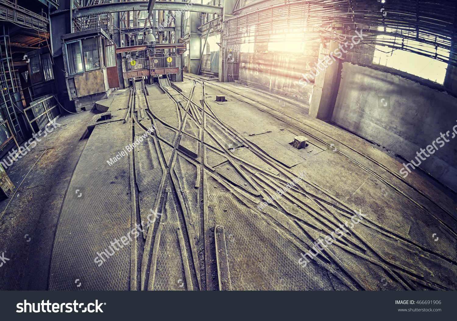 vintage toned fisheye lens picture of abandoned industrial hall interior with trolley tracks. Black Bedroom Furniture Sets. Home Design Ideas