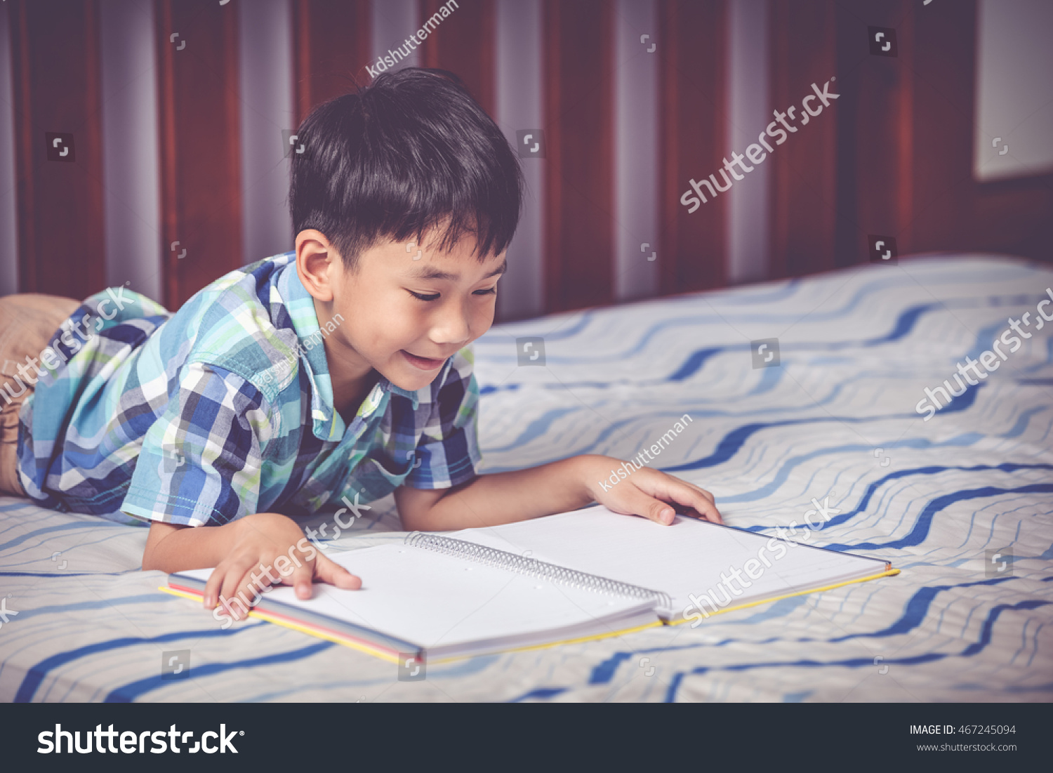 Things Your Kid s Principal Won t Tell You   Reader s Digest Lovely smiling female student doing homework lying on the floor in the  living room   Stock