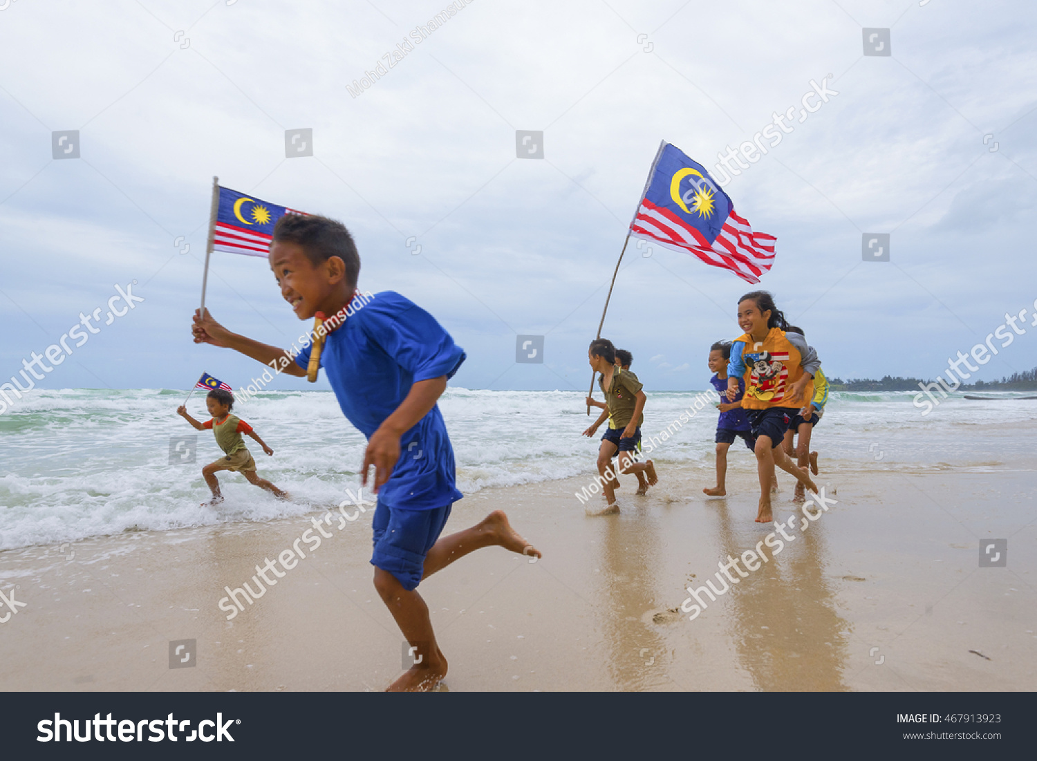 KUDAT SABAH MALAYSIA 6th AUGUST 2016 Independence Day Merdeka day concept The local kids holding a Malaysian flag running on beach