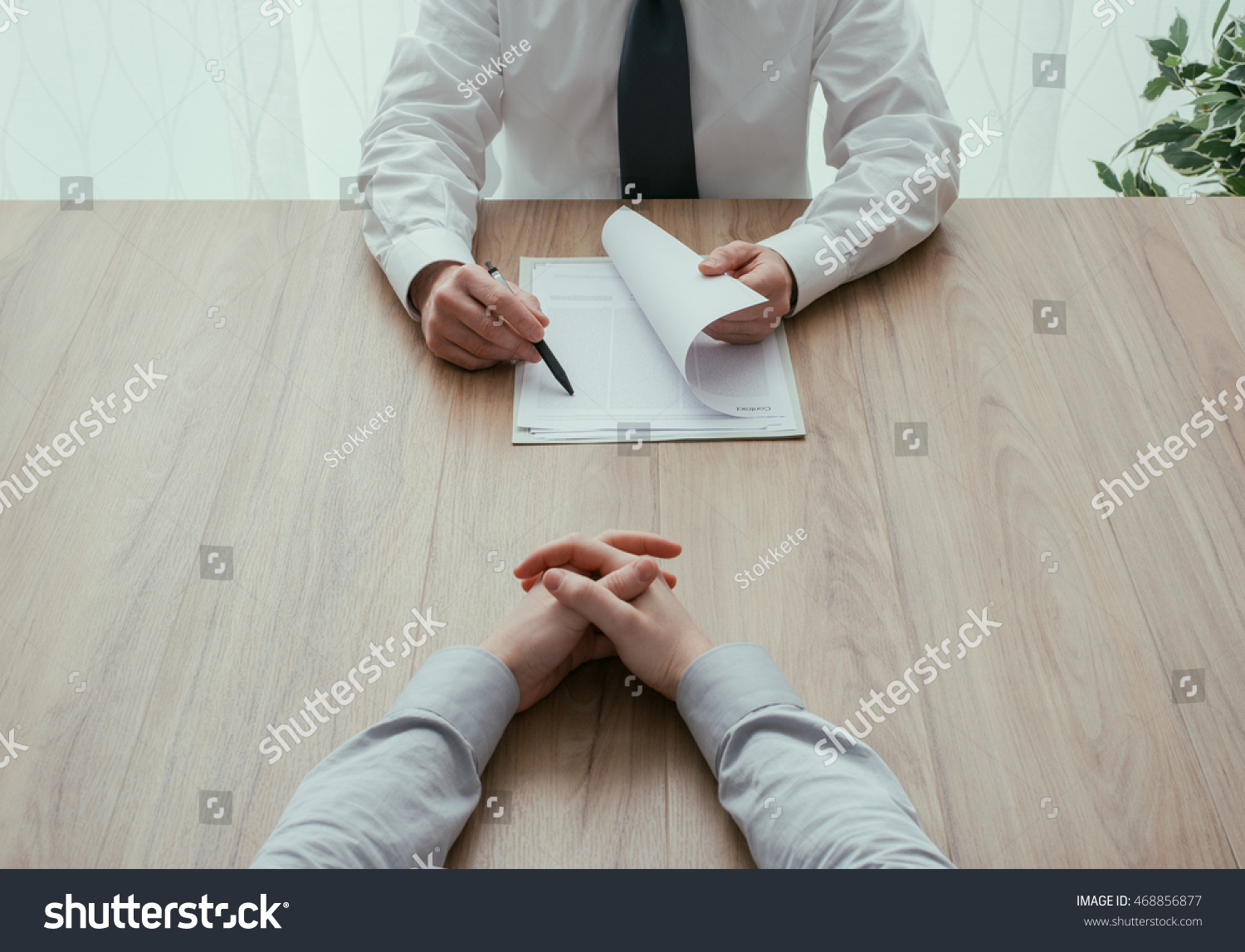 Examiner reading a resume during a job interview, employment and recruitment concept, point of view shot #468856877