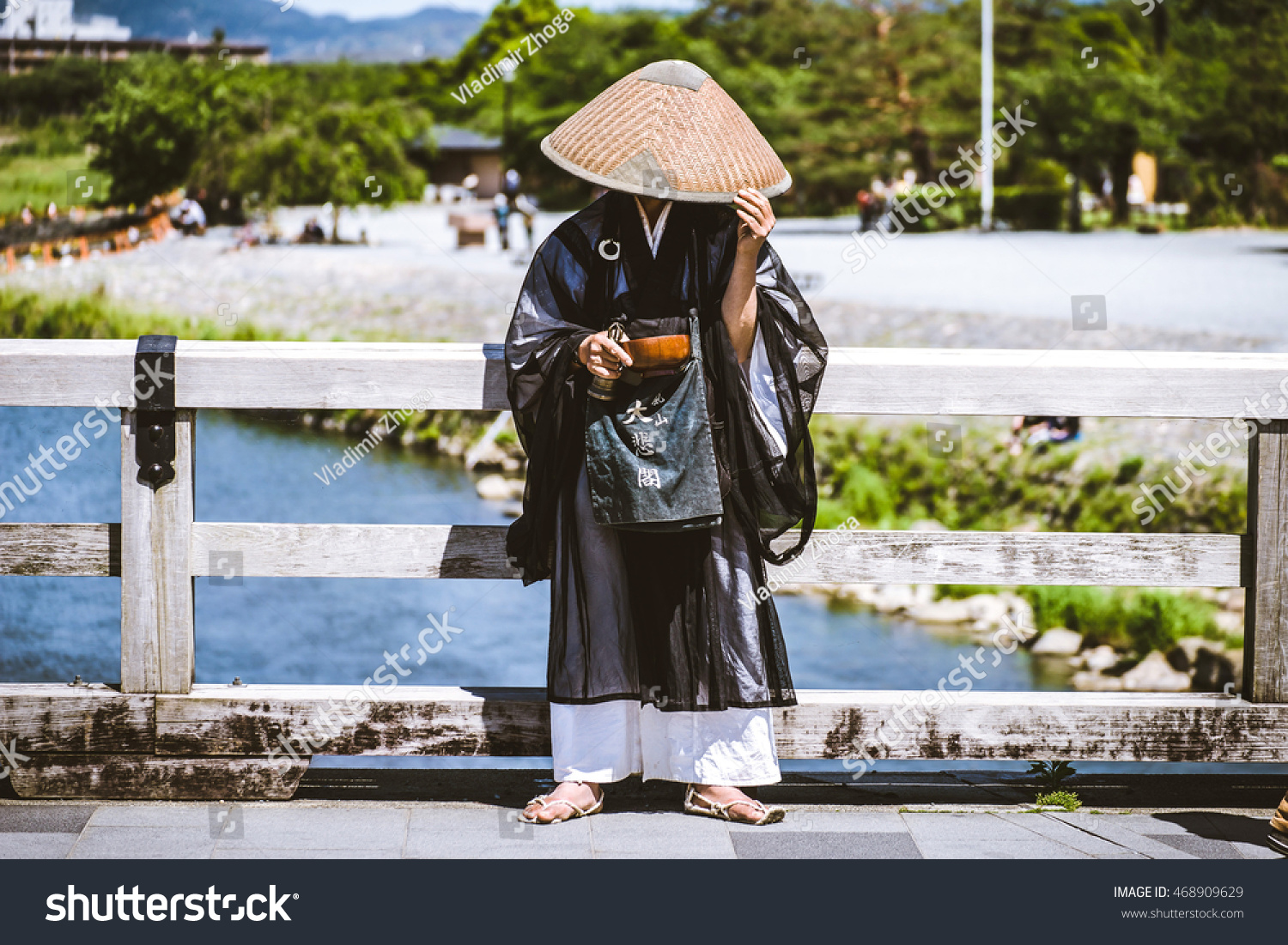 KYOTO JAPAN MAY 17 2014 Japanese artist wearing traditional costume and big hat hiding his face stands on the street of Kyoto with a wooden bowl