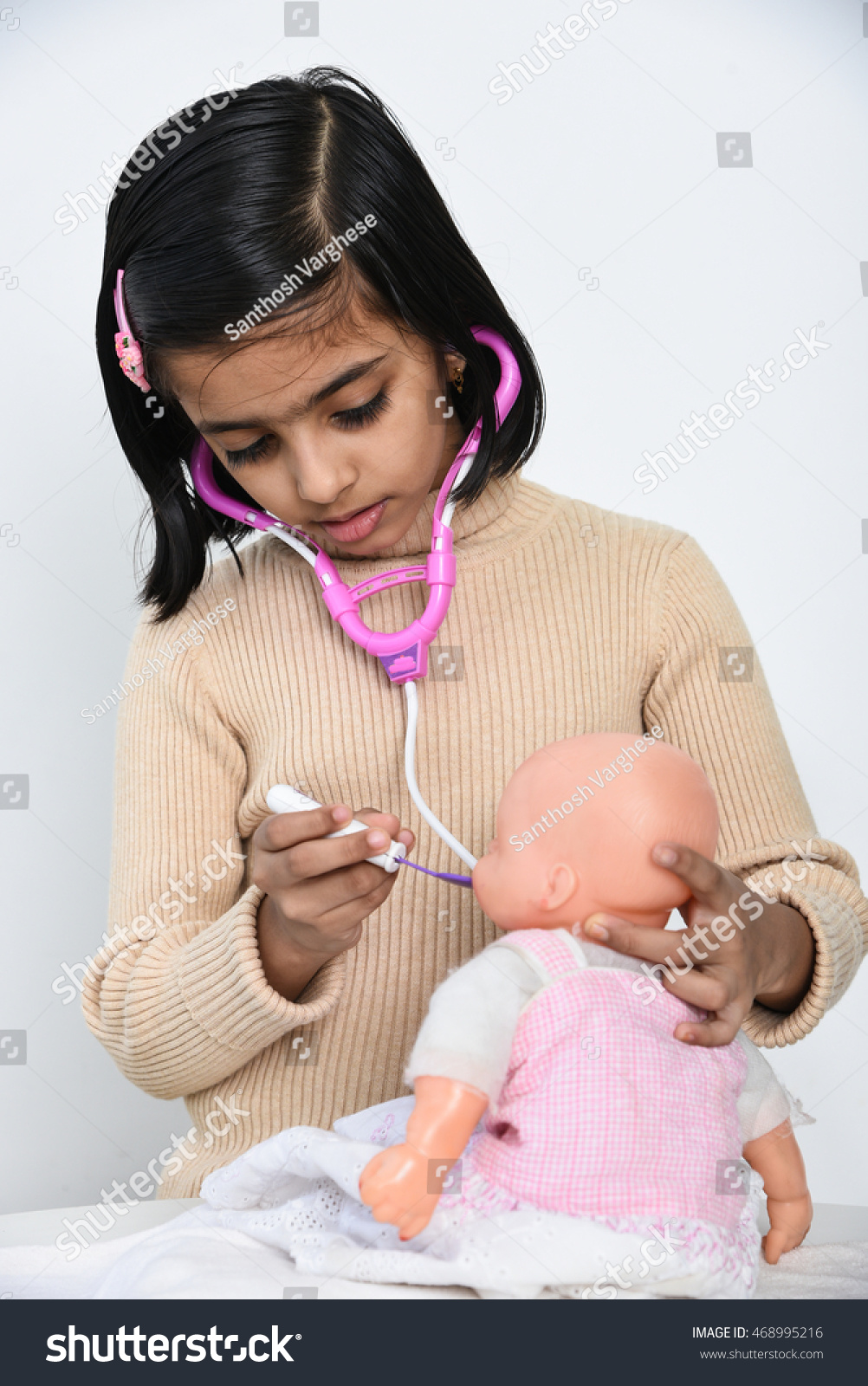 Cute young smiling happy indian girl kid playing with doctor set examining patient baby